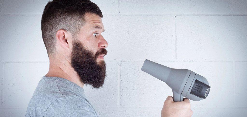 homem usando secador para secar a barba